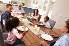 Multigeneratie zwarte familie die een maaltijd in de keuken dienen royalty-vrije stock foto