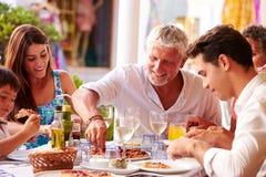 Multigeneratiefamilie die Maaltijd eten bij Openluchtrestaurant stock foto