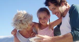 Multigeneratiefamilie die mobiele telefoon met behulp van bij strand stock video