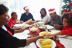 Multigeneratiefamilie die vóór Kerstmismaaltijd bidden Royalty-vrije Stock Afbeeldingen