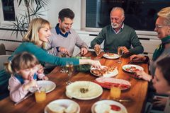 Multigeneratiefamilie die van maaltijd genieten rond lijst royalty-vrije stock afbeelding