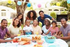 Multigeneratiefamilie die van Maaltijd in Tuin samen genieten Stock Foto's