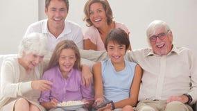 Multigeneration семья на кресле смотря ТВ сток-видео