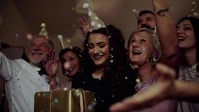 Ένα πορτρέτο της multigeneration οικογένειας με ένα κέικ σε μια εσωτερική γιορτή γενεθλίων, πτώση κομφετί απόθεμα βίντεο