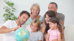Multigeneration family all looking at globe Stock Photos