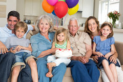 Multigeneration family celebrating girls birthday. Portrait of multigeneration family celebrating girls birthday in living room Stock Photography