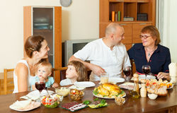 Multigeneration family communicate over table. Portrait of happy multigeneration family communicate over holiday table at home interior Royalty Free Stock Photography