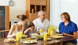 Multigeneration family  eating fish with vegetables. At home together Royalty Free Stock Photo