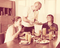 Multigeneration family  eating at home. Multigeneration family  eating fish with vegetables Stock Photos