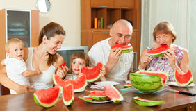 Multigeneration family  eating watermelon. Smiling multigeneration family  eating watermelon at home Royalty Free Stock Photos