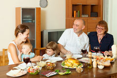 Multigeneration family having holiday dinner. Happy multigeneration family having holiday dinner at home together Stock Photos