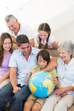 Multigeneration family looking at globe Royalty Free Stock Photography