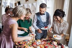 Multigeneration family putting food on plates on a indoor family birthday party. A multigeneration family putting food on plates on a indoor family birthday stock photo