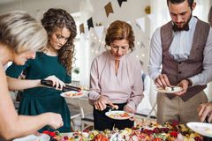 Multigeneration family putting food on plates on a indoor family birthday party. A multigeneration family putting food on plates on a indoor family birthday royalty free stock photo