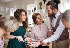 Multigeneration family putting food on plates on a indoor family birthday party. A multigeneration family putting food on plates on a indoor family birthday stock photos