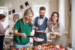 Multigeneration family putting food on plates on a indoor family birthday party. A multigeneration family putting food on plates on a indoor family birthday stock photography