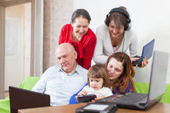 Multigeneration family uses  various electronic devices Royalty Free Stock Photo