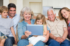 Multigeneration family using digital tablet. Happy multigeneration family using digital tablet at home Royalty Free Stock Photo