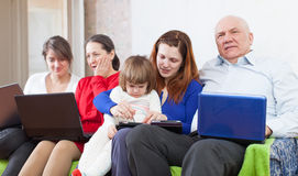 Multigeneration family using few laptops. Happy multigeneration family using few laptops Stock Photo