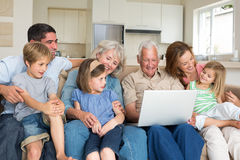 Multigeneration family using laptop in living room. Smiling multigeneration family using laptop in living room Royalty Free Stock Images