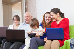 Multigeneration family using laptops. Happy multigeneration family using laptops in home Royalty Free Stock Image