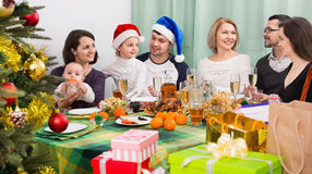 Multigenerational smiling family sitting at festive table Stock Images