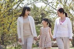 Multigenerationele familie, grootmoeder, moeder, en de handen van de dochterholding en het gaan voor een gang in het park in de le Stock Foto