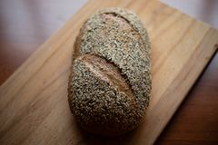 Multigrain homemade bread on a wooden cutting board at home royalty free stock photography