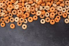 Multigrain hoops breakfast cereal border on dark grey slate Royalty Free Stock Photo