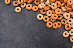 Multigrain hoops breakfast cereal diagonal border on grey slate. Multigrain hoops breakfast cereal diagonal border with copy space on a dark grey slate tile Royalty Free Stock Image
