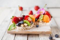 Multigrain riskakor med bär, frukt och mandeln för sunt Fotografering för Bildbyråer