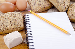 Multigrain roll and a booklet for notes Royalty Free Stock Photography