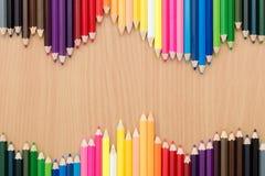 Multikleurenpotloden op houten lijst stock afbeeldingen