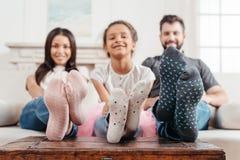 Multikulturelle Familie in den bunten Socken, die zusammen auf Sofa sitzen Stockfotos