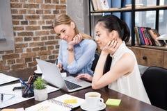 Multikulturelle Geschäftsfrauen, die mit Laptop arbeiten und am Arbeitsplatz sitzen Lizenzfreie Stockfotografie