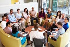 Multikulturelles Büropersonal, das zusammen sich treffen habend sitzt Stockfoto