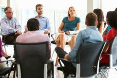 Multikulturelles Büropersonal, das zusammen sich treffen habend sitzt Stockbilder