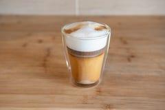 Multilayer cappuccino w szklanej filiżance na drewnianym stole lub kawa Obraz Royalty Free