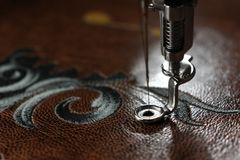 Multilayer embroidery on brown leatherette with embroidery machine - close up with needle up Stock Photo