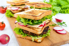 Multilayered sandwiches with a juicy cutlet, cheese, radish, cucumber, lettuce, arugula on a cutting board Stock Photos