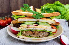 Multilayered sandwiches with a juicy cutlet, cheese, radish, cucumber, lettuce, arugula cutting in half on a plate. On a dark wooden background Stock Photos