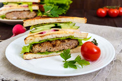Multilayered sandwiches with a juicy cutlet, cheese, radish, cucumber, lettuce, arugula. Cutting in half on a plate on a dark wooden background. Close up Royalty Free Stock Images