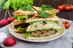 Multilayered sandwiches with a juicy cutlet, cheese, radish, cucumber, lettuce, arugula. Cutting in half on a plate on a dark wooden background Royalty Free Stock Image