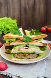 Multilayered sandwiches with a juicy cutlet, cheese, radish, cucumber, lettuce, arugula. Cutting in half on a plate on a dark wooden background. Vertical view Royalty Free Stock Photography