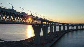 Multilevel highway bridge on background evening evening sunset at sea. Beautiful view from flying drone car moving on modern multilevel highway over river water stock footage