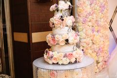 Multilevel wedding cake decorated with flowers stands on a table. Concept of eating, sweets and desserts at a party. Multilevel wedding cake decorated with stock images