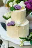 The multilevel wedding cake with lilac on the table Stock Images