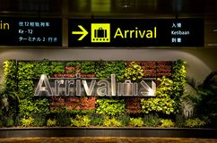 Multilingual arrival sign and flowers at airport Royalty Free Stock Image