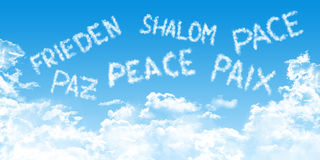 Multilingual peace message with cloud fonts on blue heaven background. Multilingual peace message written with cloud fonts on blue heaven background stock photography
