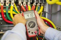 Multimètre dans des mains d'électricien en plan rapproché à haute tension de boîte de liaison triphasée de puissance Mains d'ingé images stock